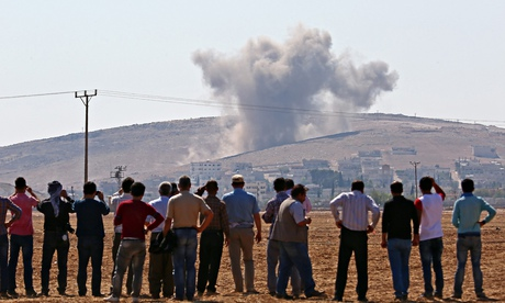 Local residents in the Suruc district of Sanliurfa, Turkey, watch smoke rising from the Syrian borde